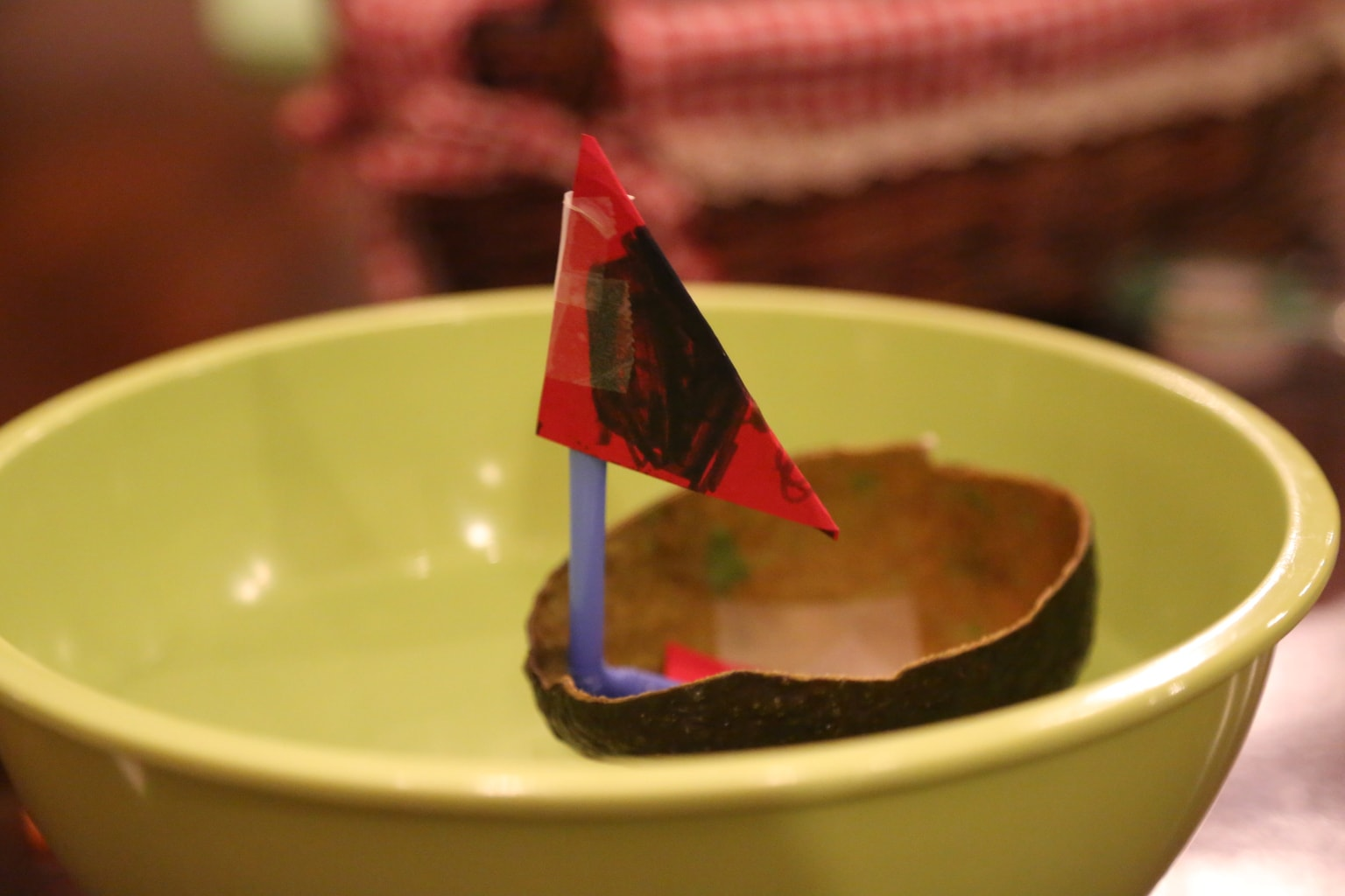 little boat made of avocado peel floating in bowl full of water
