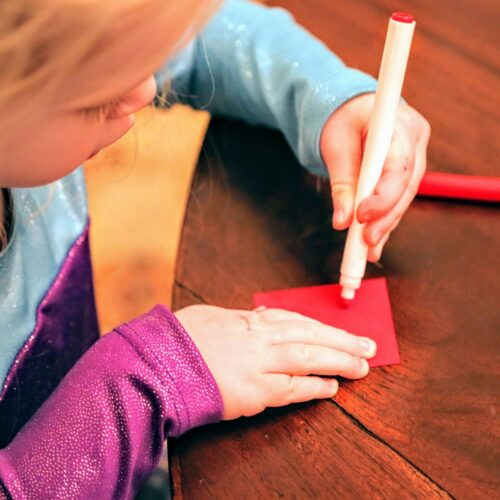 child coloring red square of paper
