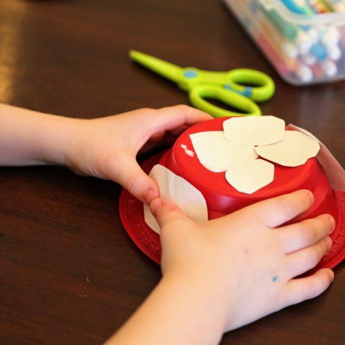 child gluing white spots to mushroom house