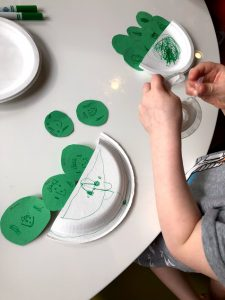 Child taping paper peas onto paper plate for peas in a pod craft