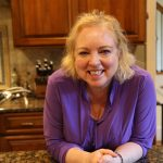 woman with blonde hair and purple blouse smiling and leaning on kitchen counter