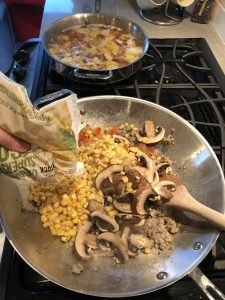 Adding corn to mushroom mixture