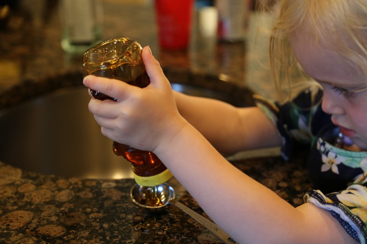 Child measuring honey