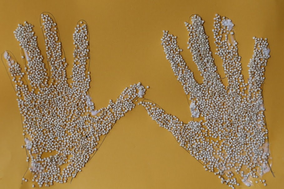 traced hands with glued quinoa