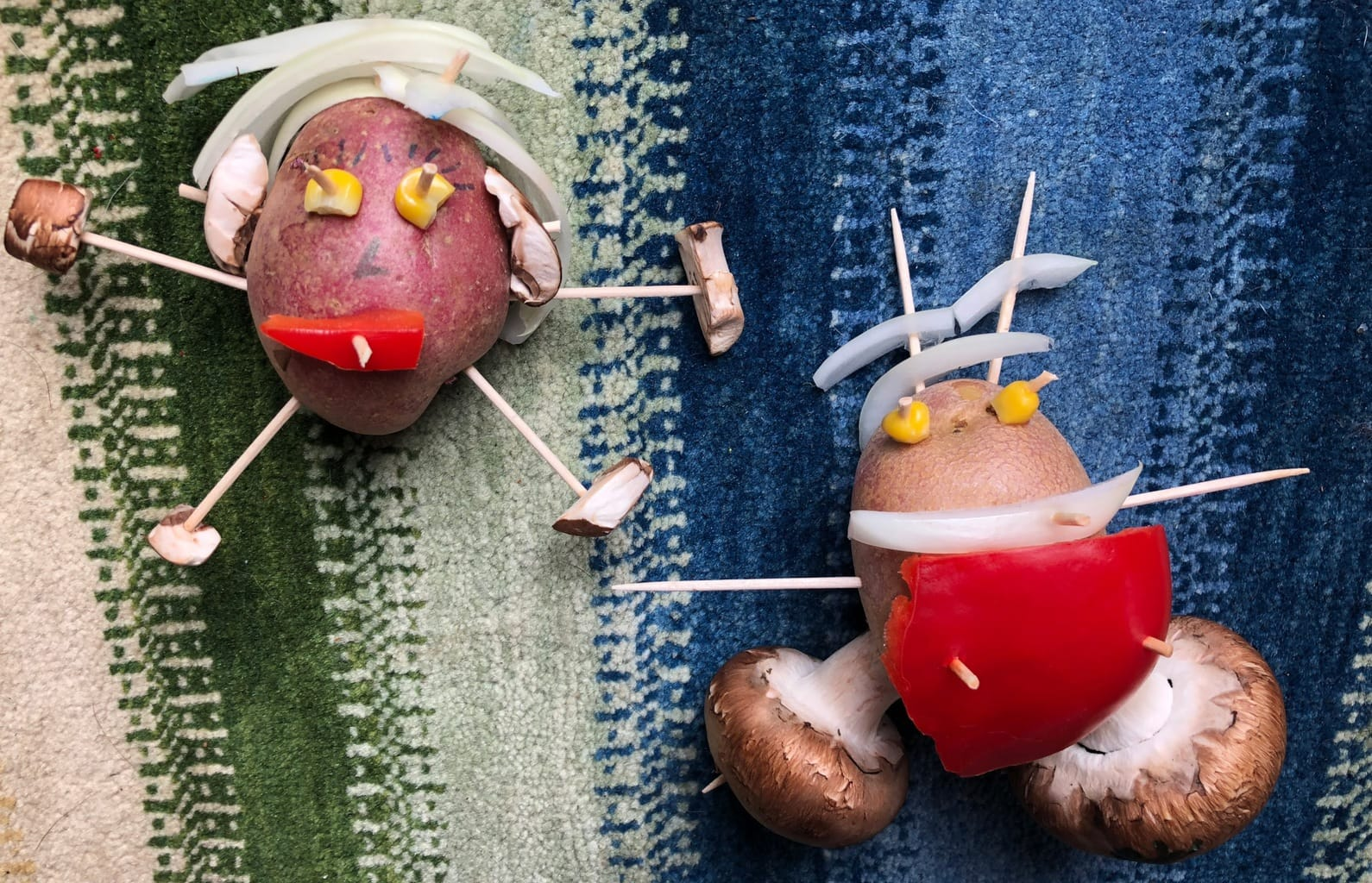 2 potatoes dressed as people using toothpicks, onions and peppers