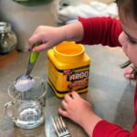 Child scooping up cornstarch