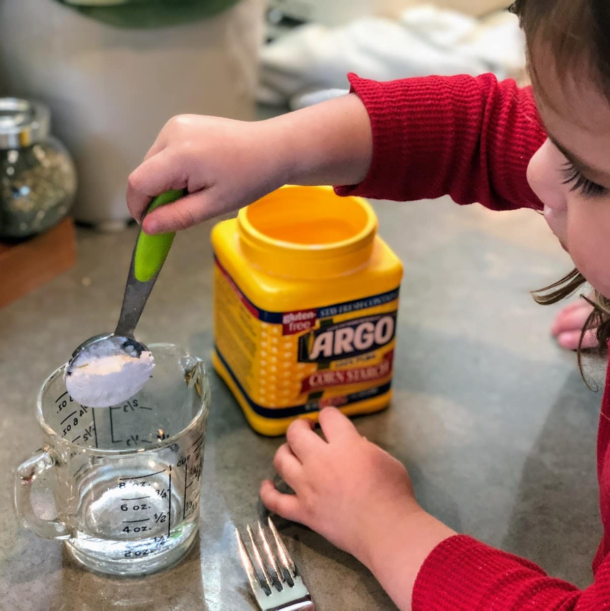 Child scooping up cornstarch