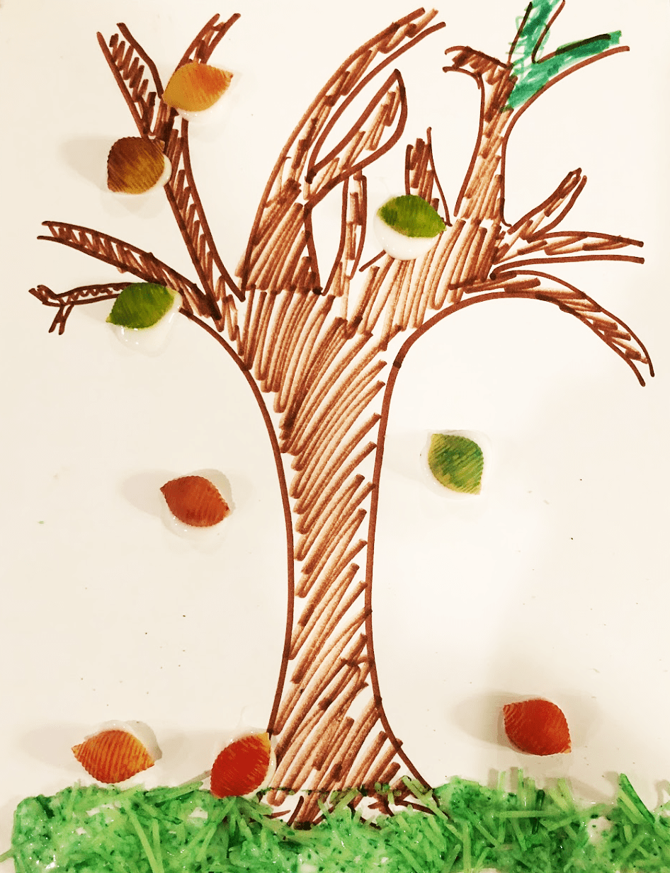 tree drawn on paper with colored shell noodles as leaves and green-dyed parmesan as grass