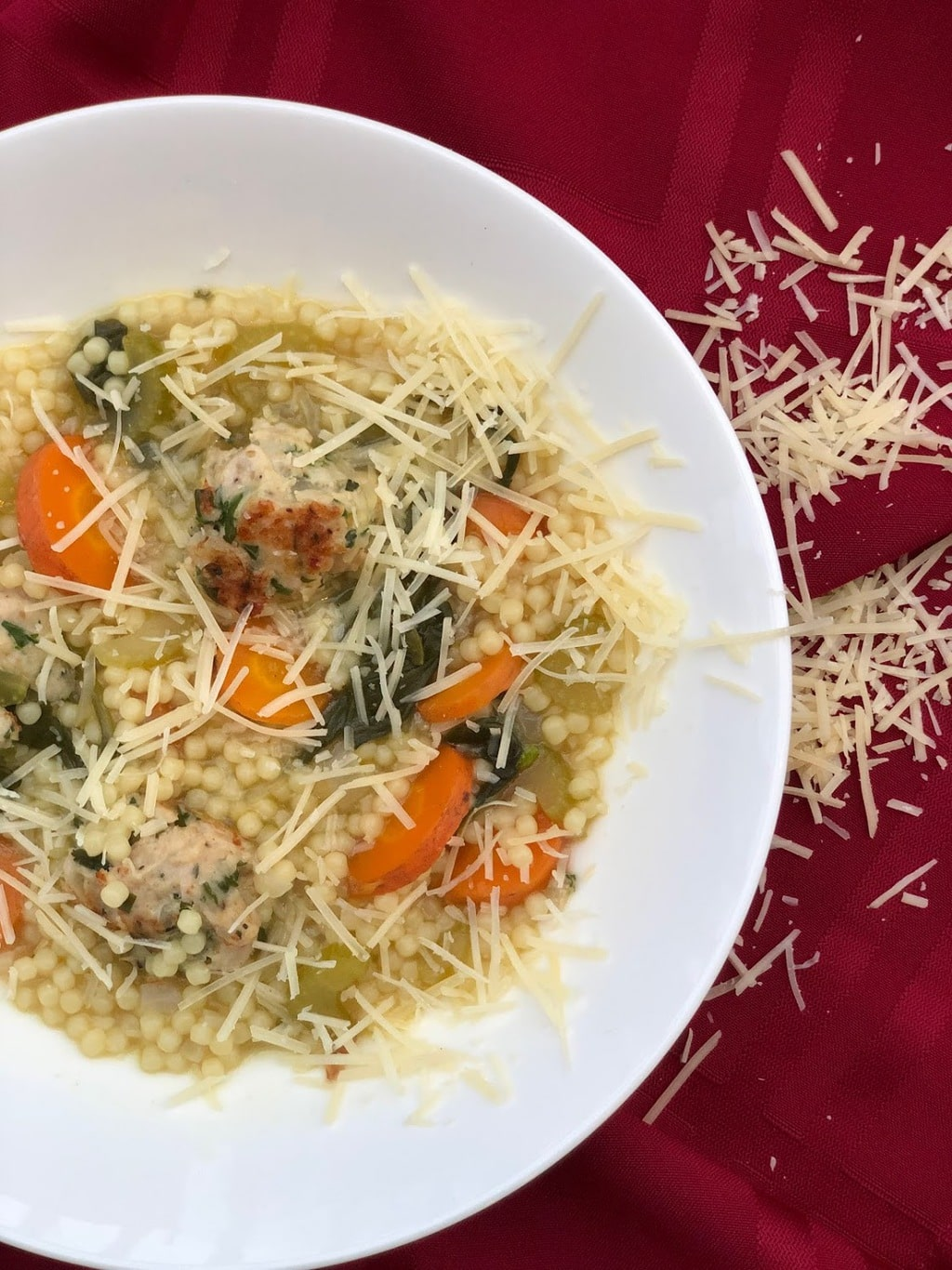 Italian wedding soup in bowl with shredded parmesan cheese