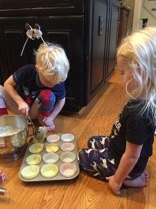 kids baking muffins on kitchen floor