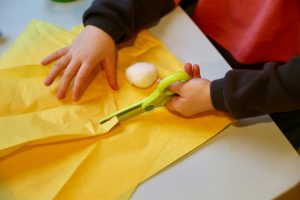 Child cutting yellow tissue paper