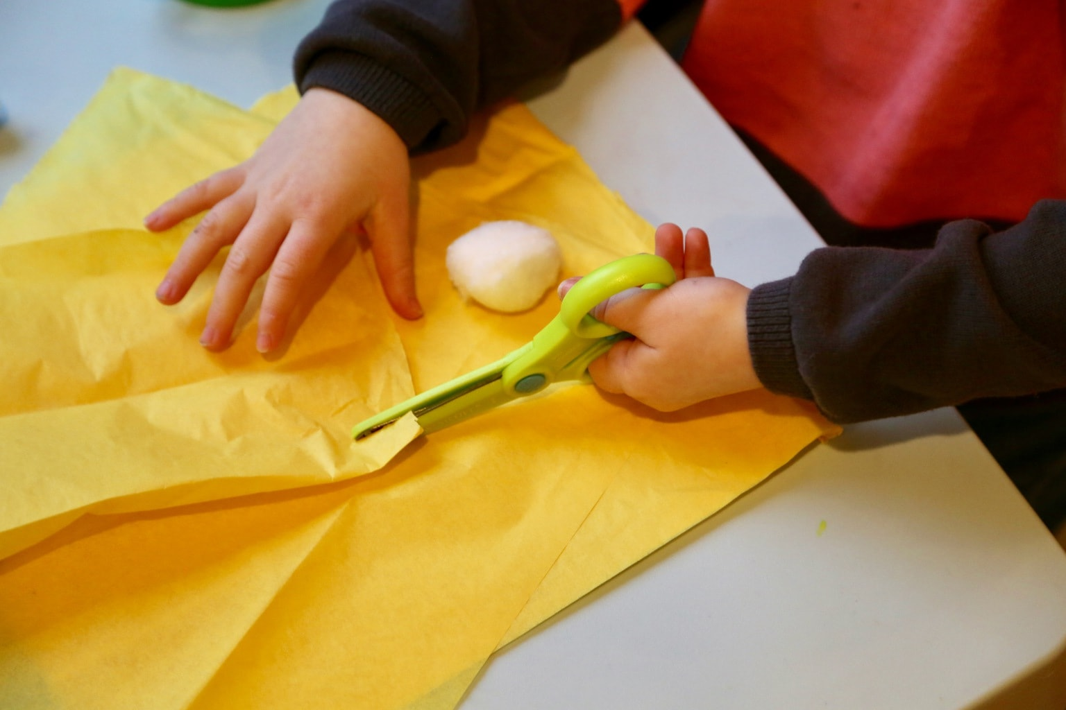 Child cutting yellow tissue paper for play food tortellini