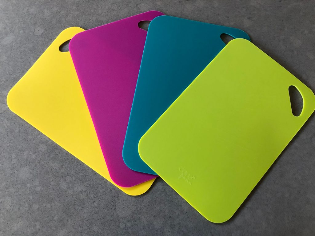 yellow, pink, blue and green Core cutting boards fanned out on counter