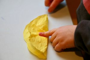Child folding yellow circle over cotton ball