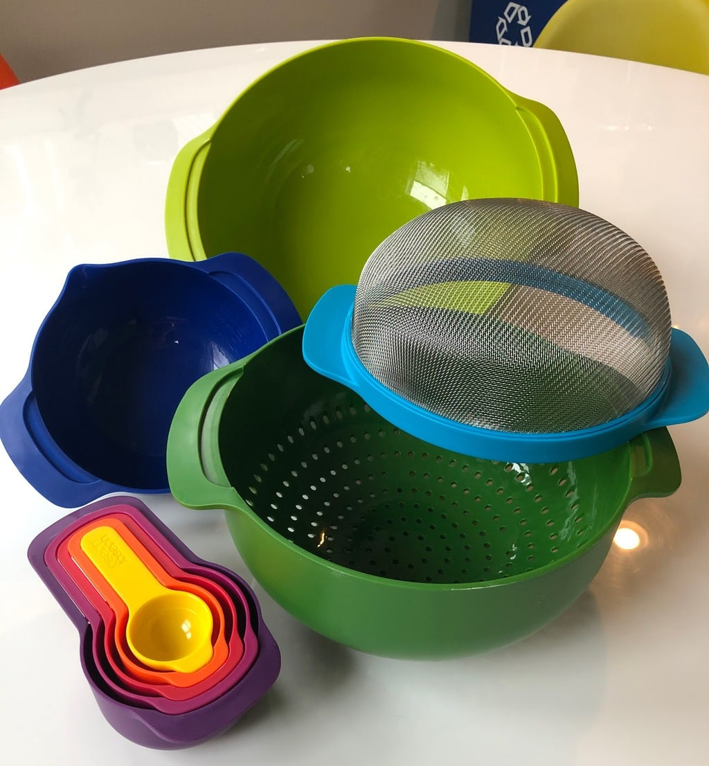 set of colorful nesting bowls, measuring cups and strainers spread out on white table