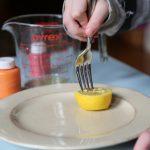 child stabbing lemon with fork