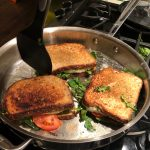 three pesto paninis toasting in pan with spatula about to flip one over