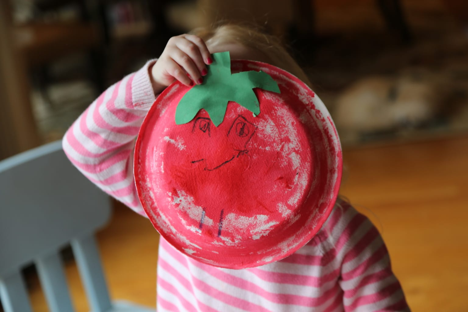 child holding paper plate tomato over her face