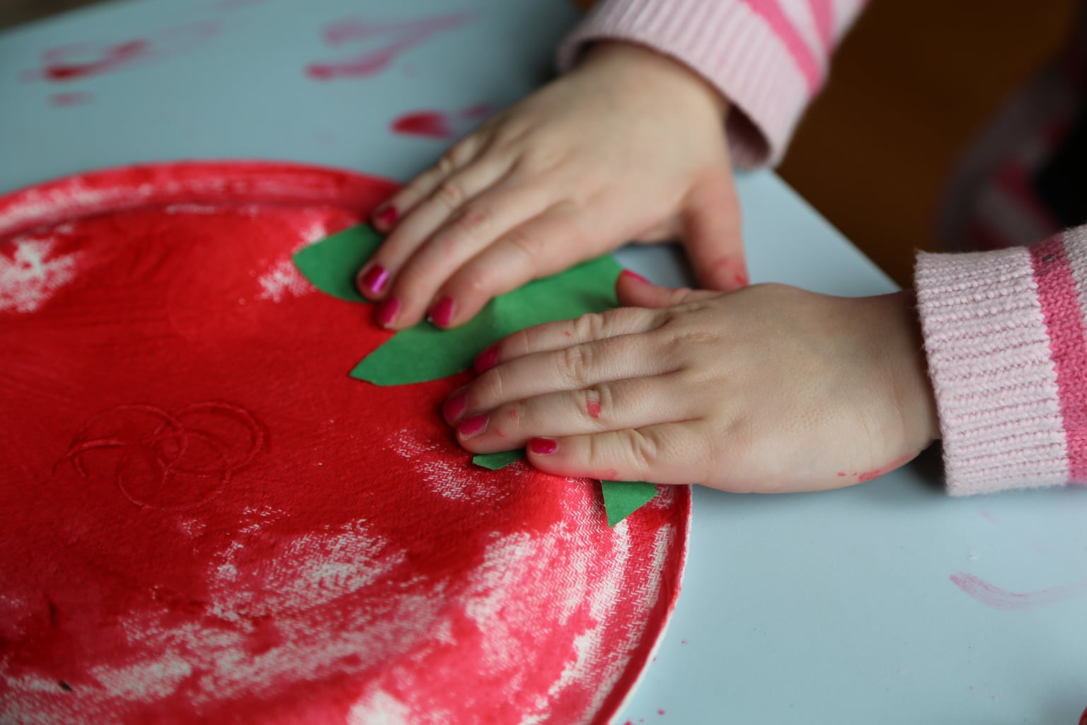 Child pasting stem onto plate