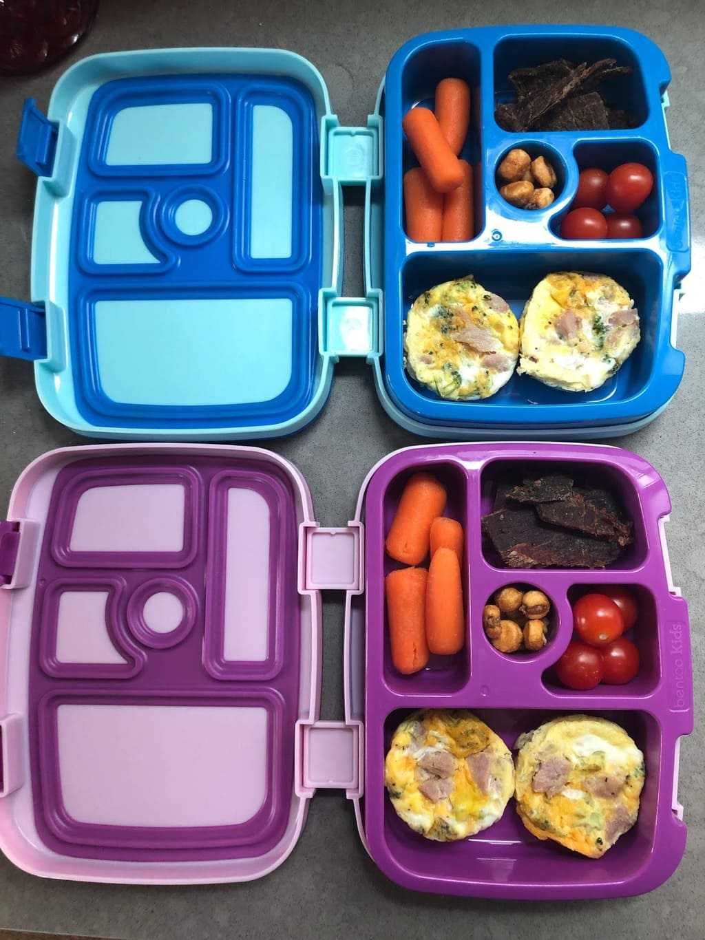 a blue and purple lunchbox with mini egg bites and other snacks