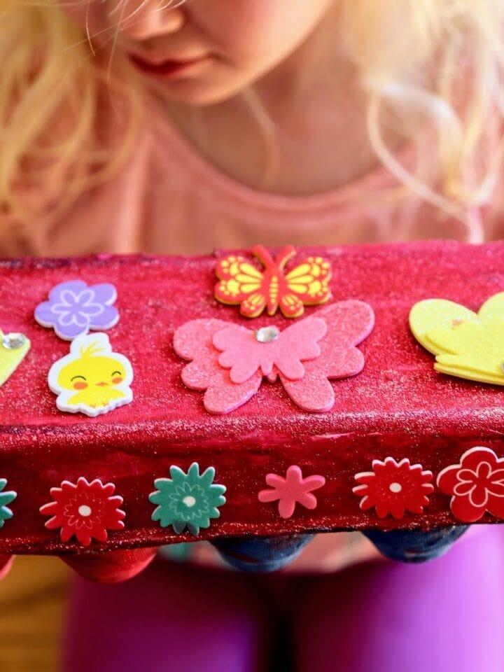 child holding egg carton treasure chest
