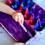 child painting inside egg carton purple