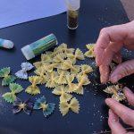 Sprinkling glitter on pasta butterflies