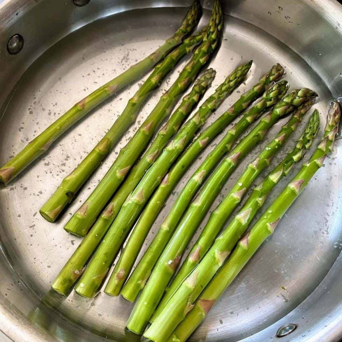 asparagus in shallow water in medium pan