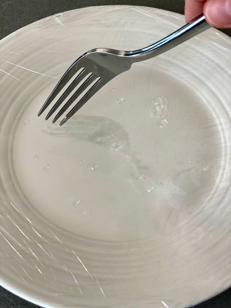white plate wrapped in plastic wrap with fork poking holes in top