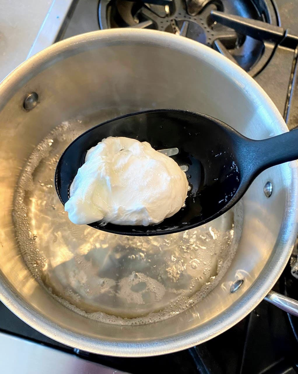 slotted spoon getting poached egg out of pot