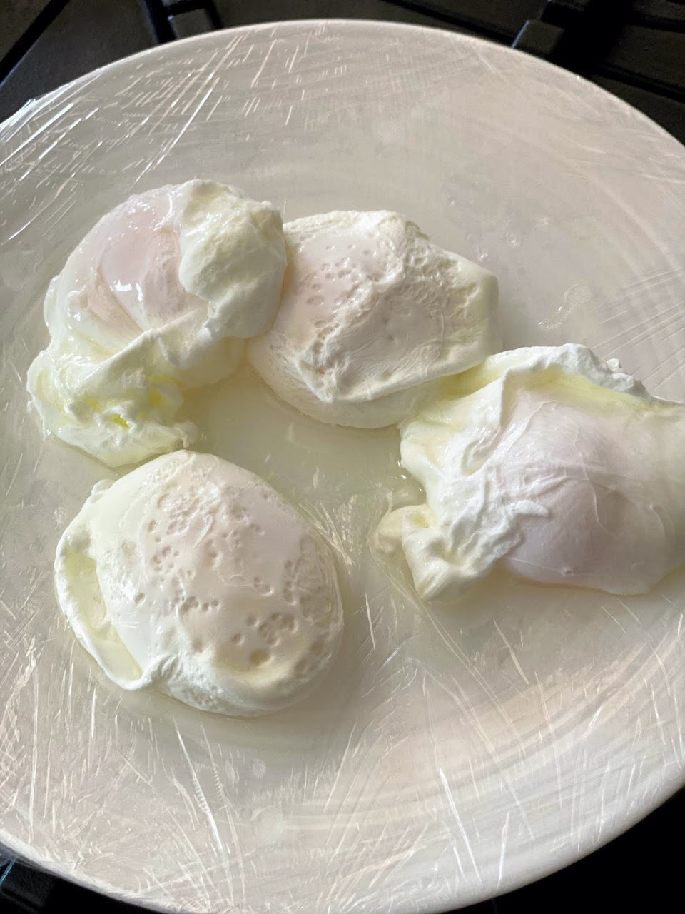 four poached eggs sitting on plastic-wrapped plate