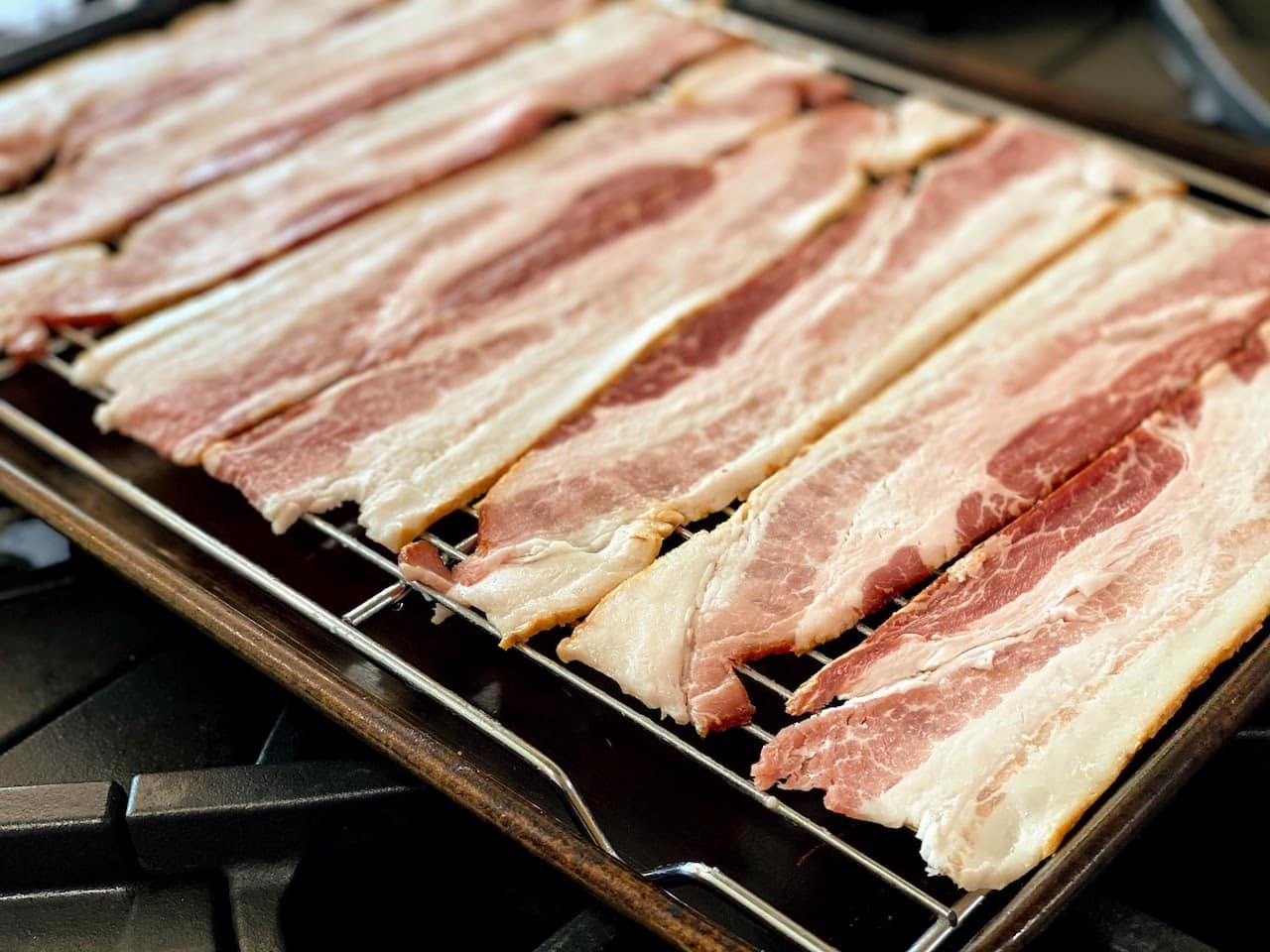 strips on raw bacon on wire rack in rimmed baking sheet