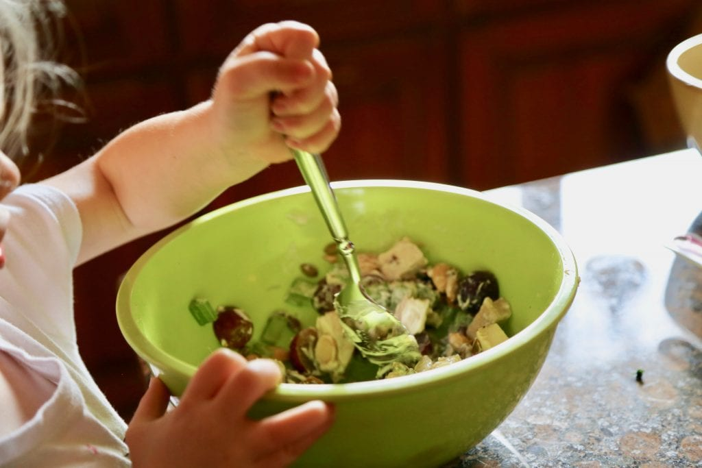 child mixing chicken salad in bowl