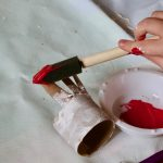 child painting chicken's comb red
