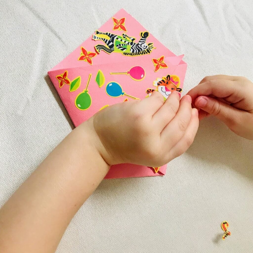 child decorating origami chip bag with stickers