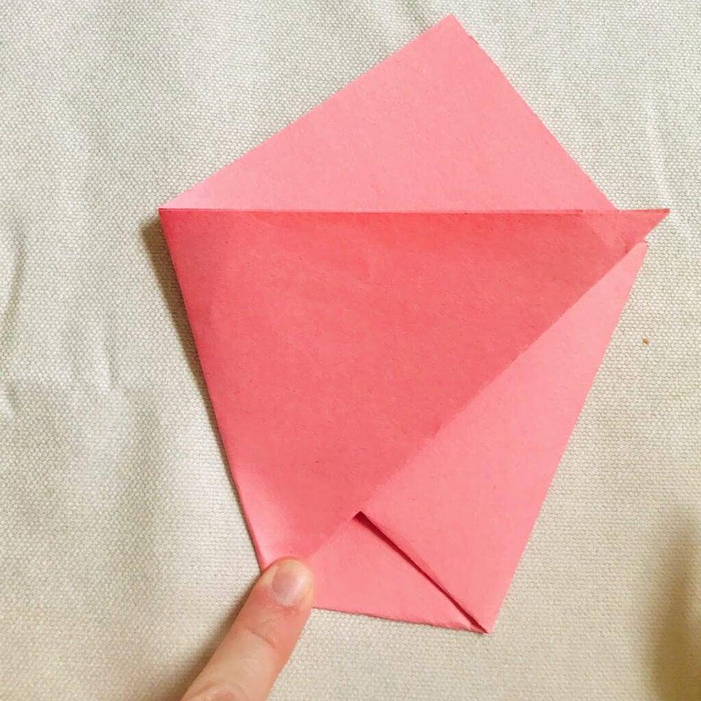 child securing origami paper bag closed