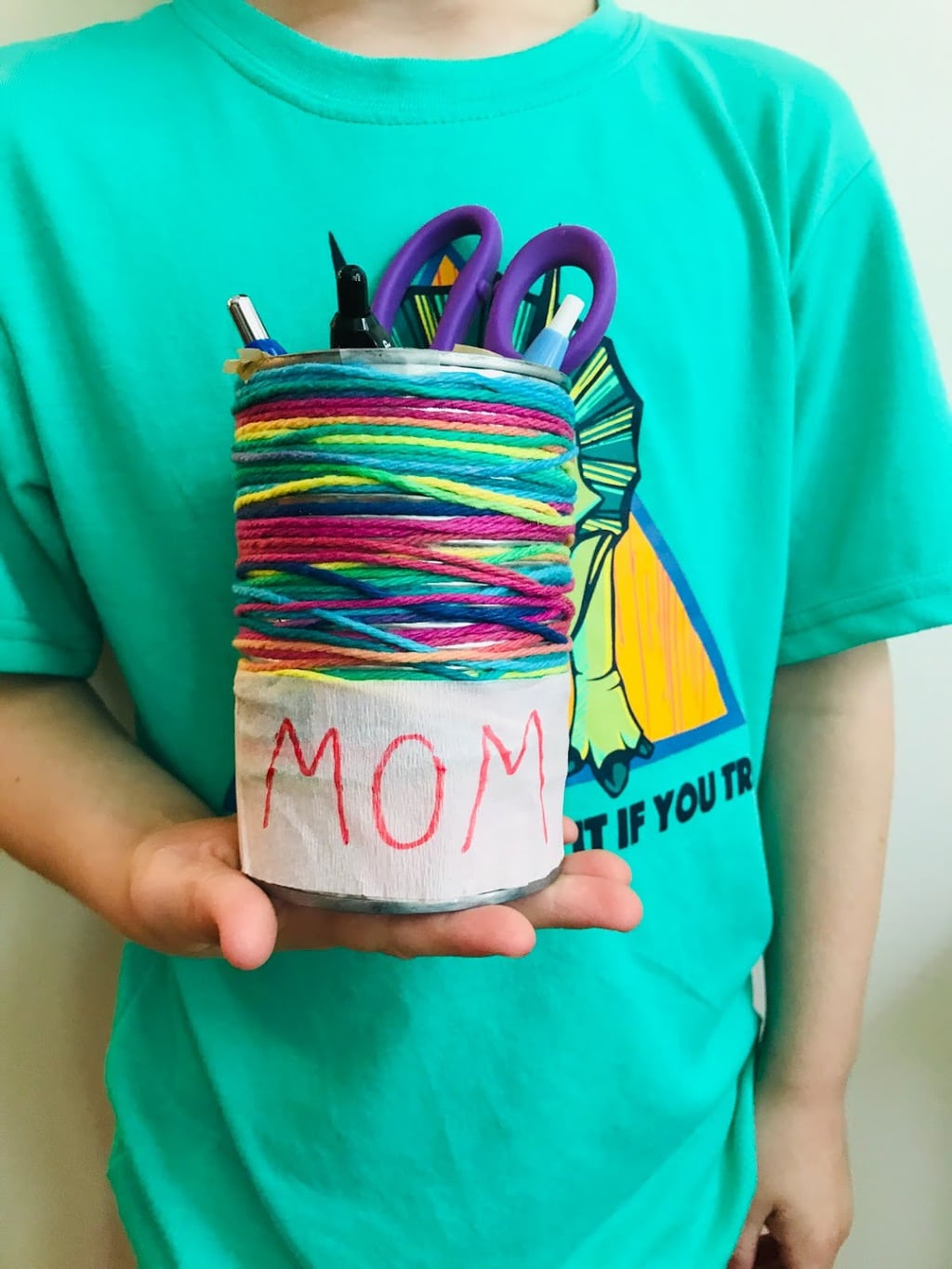 child holding can pencil holder