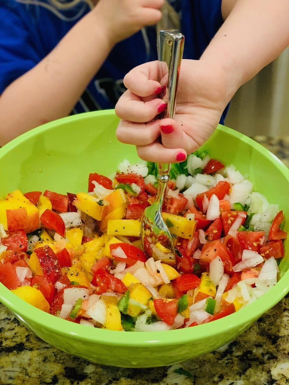 child stirring peach salsa