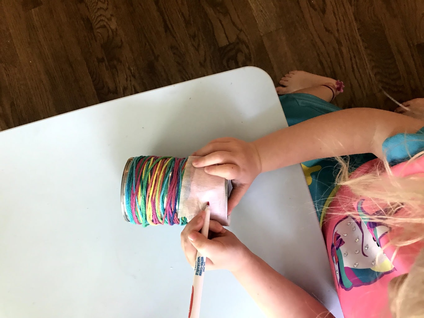 child writing on can pencil holder