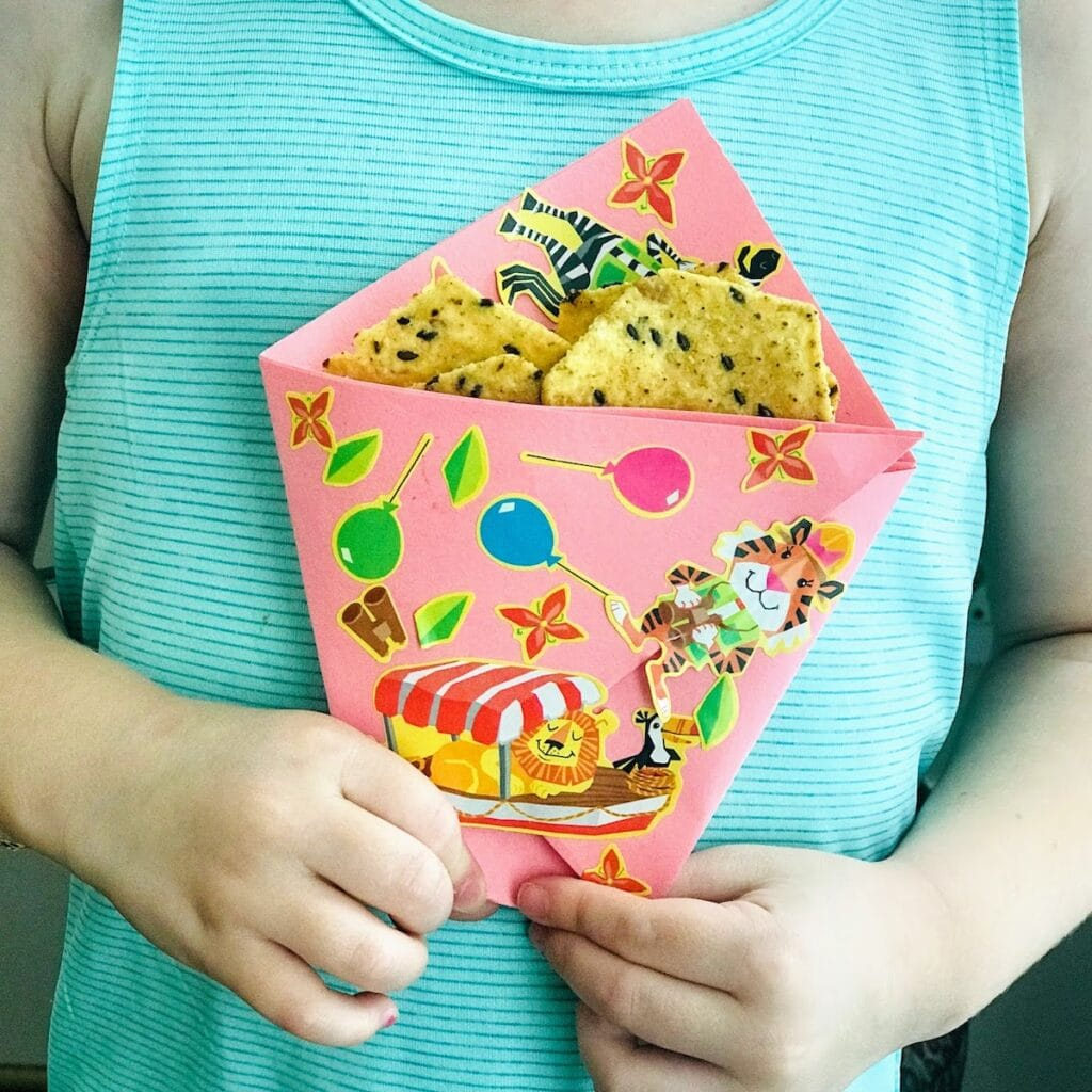 child holding origami paper bag with chips