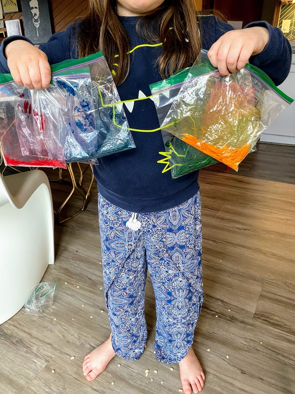 child holding 5 ziploc bags of colored broken spaghetti noodles