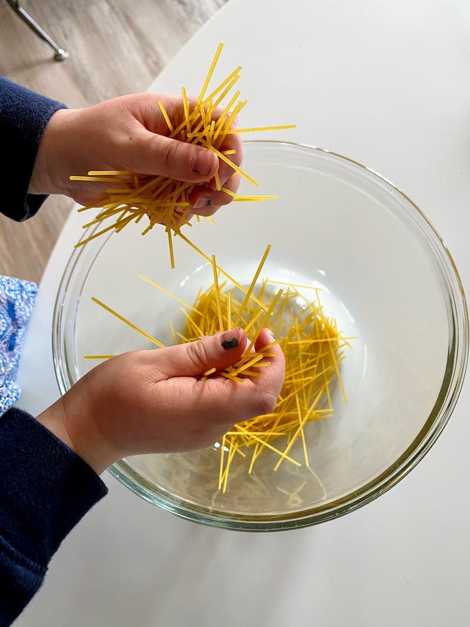 child breaking up spaghetti noodles over clear bowl
