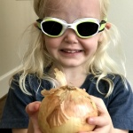 Child smiling, wearing goggles and holding an onion