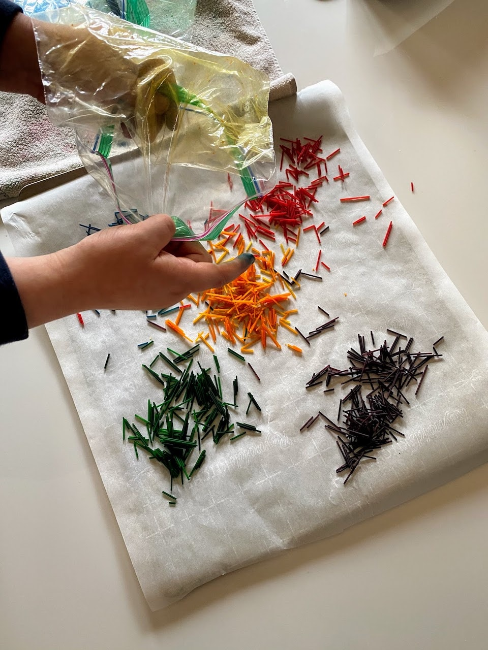 emptying bags of colored spaghetti noodles onto baking sheet to dry