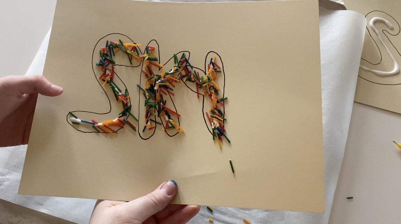 the word sky in rainbow sprinkles on tan paper