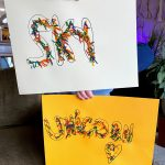 child holding rainbow spaghetti art with words sky and unicorn