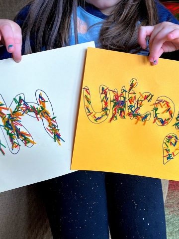 child holding rainbow spaghetti art with words sky and unicorn
