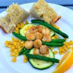 Seared Scallops with Summer Veggies and Garlic Bread on plate