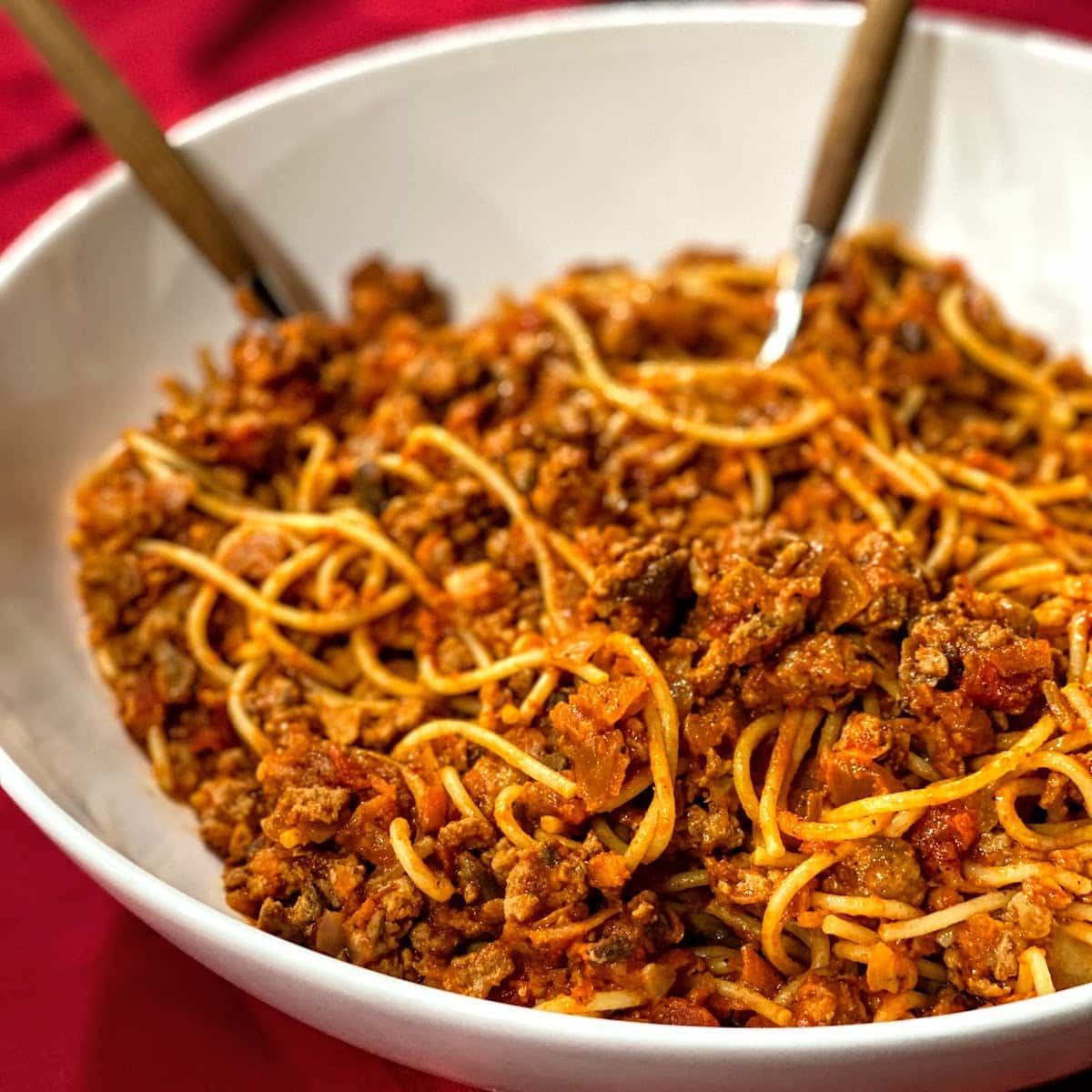 white, big bowl of spaghetti with meat sauce on red tablecloth