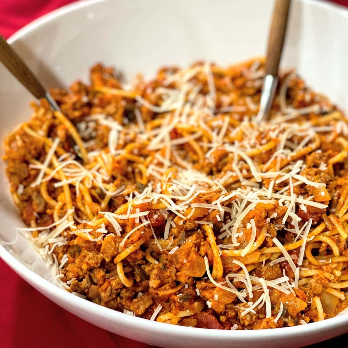 white, big bowl of spaghetti with meat sauce and cheese on red tablecloth